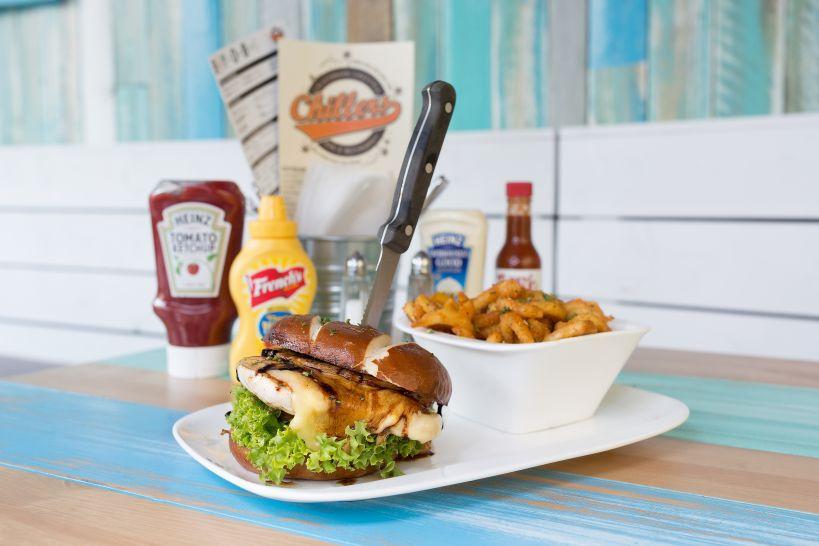 Banzai Burger auf Soft Pretzel Bun mit Grilled Chicken Patty und einer Side Curly Fries