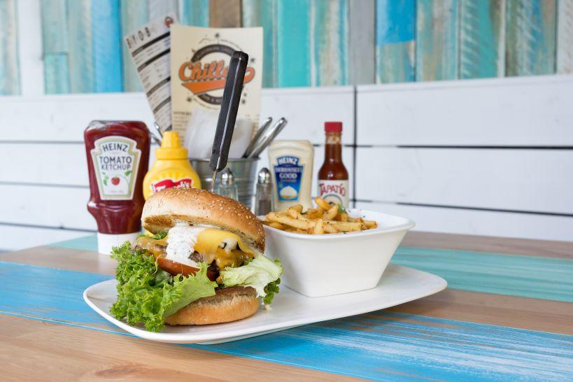 Cheezy Bro Burger auf Sourdough Bun mit Beef Patty und einer Side Onion Rings