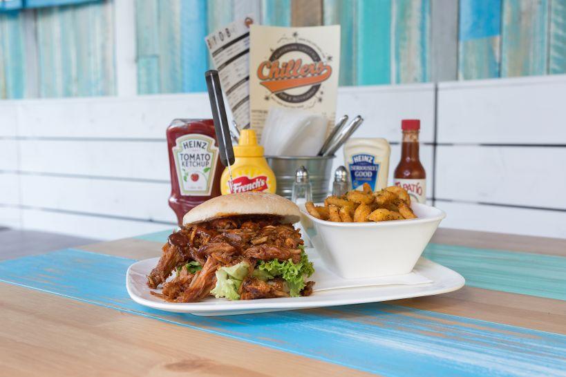 Classic Burger auf CHILLERS Bun mit Pulled Pork und einer Side Curly Fries