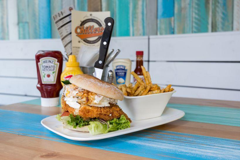 Tasty Schwasty Burger auf CHILLERS Bun mit Fried Chicken Patty und einer Side French Fries